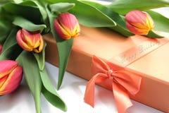 Tulipani gialli arancio, contenitore di regalo e testo di buon compleanno sul ciclo fotografie stock libere da diritti