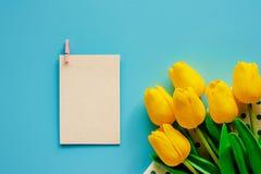 Tulipani gialli artificiali con la carta del Libro Bianco su backgroun blu fotografia stock