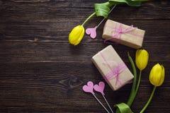 Tulipani gialli con i contenitori di regalo e cuori decorativi su legno scuro Fotografia Stock