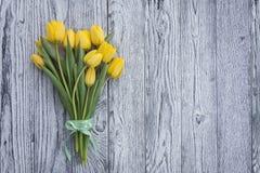 Tulipani gialli con il nastro su fondo di legno Immagini Stock