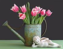 Tulipani in latta di innaffiatura con il Cherub Immagine Stock