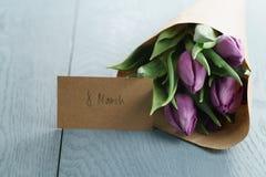 Tulipani porpora in carta del mestiere su fondo di legno blu Immagine Stock Libera da Diritti