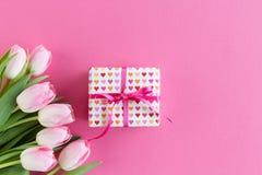 Tulipani rosa su fondo rosa con il contenitore di regalo fotografie stock
