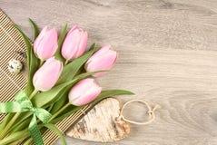 Tulipani rosa, uovo di quaglia e cuore di legno sulla tavola, spazio per il vostro Fotografia Stock