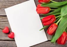 Tulipani rossi, carta in bianco e cuori della caramella Immagine Stock