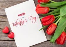 Tulipani rossi, carta in bianco e cuori della caramella Fotografie Stock Libere da Diritti