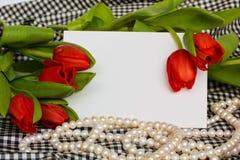 Tulipani rossi con il filo delle perle e la scheda in bianco Immagini Stock
