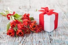 Tulipani rossi con il regalo sulle plance di legno Fotografia Stock Libera da Diritti