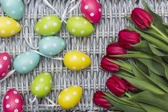 Tulipani rossi con le foglie verdi, uova tinte variopinte di Pasqua Immagine Stock Libera da Diritti