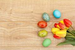 Tulipani rossi e gialli dipinti delle uova di Pasqua, sui bordi di legno Immagini Stock