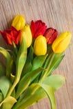 Tulipani rossi e gialli su una tavola di legno Immagine Stock Libera da Diritti