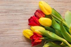 Tulipani rossi e gialli su una tavola di legno Fotografia Stock Libera da Diritti