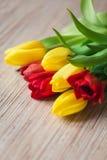 Tulipani rossi e gialli su una tavola di legno Fotografie Stock Libere da Diritti