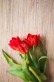 Tulipani rossi su una tavola di legno Immagine Stock Libera da Diritti