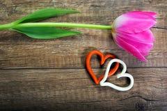 Tulipano e cuori su un fondo di legno immagine stock