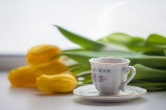 tulipano giallo e una tazza di tè o di caffè caldo Fotografia Stock