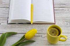 Tulipano giallo, tazza di tè e taccuino Immagini Stock