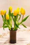 Tulipanowy bukiet z dużo kwitnie jako Wielkanocna dekoracja w brown flowerpot na stole z białym tablecloth Zdjęcie Royalty Free