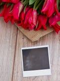 Tulipany na drewnianym stole z natychmiastowym foto Zdjęcie Stock