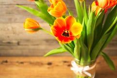 Tulipas alaranjadas bonitas em um vaso em um fundo de madeira marrom Idealmente um humor da mola para senhoras bonitas Imagem de Stock Royalty Free