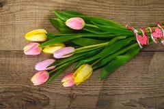Tulipas amarelas e cor-de-rosa na madeira Imagens de Stock