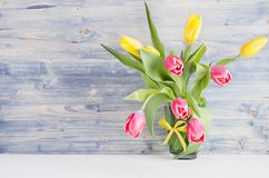 Tulipas amarelas e vermelhas no vaso na placa de madeira chique gasto azul Fundo da mola de abril, interior da casa, decoração imagens de stock