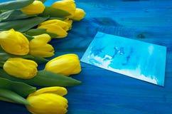 Tulipas amarelas no fundo de madeira azul com cartão Foto de Stock