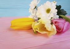 Tulipas bonitas, aniversário do crisântemo em um fundo de madeira cor-de-rosa Imagem de Stock Royalty Free