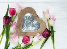 Tulipas bonitas coloridas e coração de madeira grande na tabela de madeira branca Valentim, fundo da mola fotografia de stock