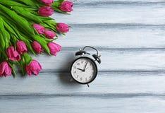Tulipas bonitas cor-de-rosa com despertador Imagens de Stock
