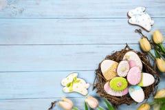 Tulipas bonitas de e com os ovos coloridos no ninho e as cookies como o coelho no fundo de madeira azul imagens de stock