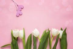 Tulipas brancas com corações decorativos no fundo cor-de-rosa Espaço FO Imagens de Stock Royalty Free