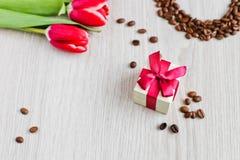 Tulipas, café da caixa de presente e milho vermelhos Fotografia de Stock