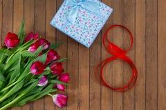 Tulipas, caixa de presente e fita na forma do número 8 Imagem de Stock
