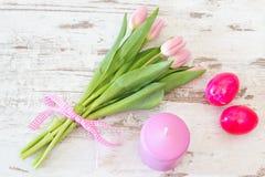 Tulipas com ovos da páscoa e vela no rosa Imagem de Stock