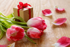 Tulipas cor-de-rosa com o presente no fundo de madeira Fotografia de Stock