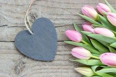 Tulipas cor-de-rosa e violetas com um coração Imagens de Stock Royalty Free