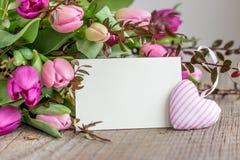 Tulipas cor-de-rosa e violetas com um coração Fotos de Stock