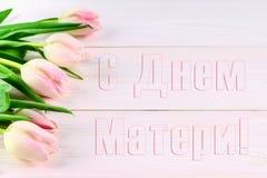 Tulipas cor-de-rosa em uma tabela de madeira branca com uma inscrição no russo - dia feliz do ` s da mãe Fotos de Stock Royalty Free