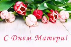 Tulipas cor-de-rosa em uma tabela de madeira branca com uma inscrição no russo - dia feliz do ` s da mãe Foto de Stock Royalty Free