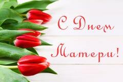 Tulipas cor-de-rosa em uma tabela de madeira branca com uma inscrição no russo - dia feliz do ` s da mãe Imagens de Stock Royalty Free