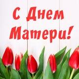 Tulipas cor-de-rosa em uma tabela de madeira branca com uma inscrição no russo - dia feliz do ` s da mãe Fotografia de Stock Royalty Free