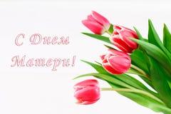 Tulipas cor-de-rosa em uma tabela de madeira branca com uma inscrição no russo - dia feliz do ` s da mãe Fotografia de Stock