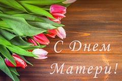 Tulipas cor-de-rosa na tabela de madeira com uma inscrição no russo - dia feliz do ` s da mãe Fotos de Stock Royalty Free