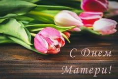 Tulipas cor-de-rosa na tabela de madeira com uma inscrição no russo - dia feliz do ` s da mãe Imagem de Stock Royalty Free
