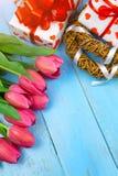 Tulipas cor-de-rosa no fundo azul de madeira Feriado da concepção, o 8 de março, dia do ` s da mãe Espaço liso da configuração e  Foto de Stock