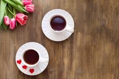 Tulipas cor-de-rosa no fundo de madeira, dois copos do chá e café em pires com doce de fruta dos corações Fotografia de Stock Royalty Free