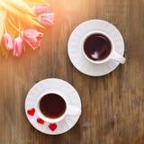 Tulipas cor-de-rosa no fundo de madeira, dois copos do chá e café em pires com doce de fruta dos corações Imagem de Stock Royalty Free