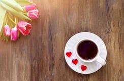 Tulipas cor-de-rosa no fundo de madeira, dois copos do chá e café em pires com doce de fruta dos corações Fotos de Stock Royalty Free