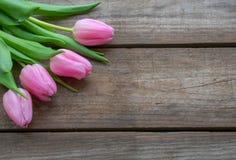 Tulipas cor-de-rosa no fundo de madeira imagem de stock